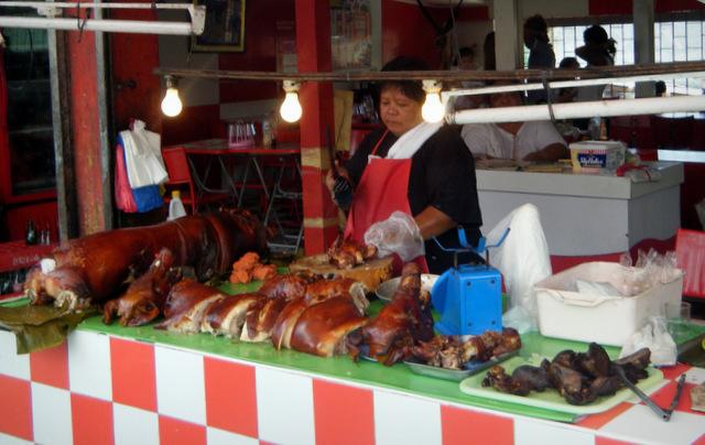 Beim Zerhacken des Schweines regnet es kleine Fleischstückchen, die sich im Haar der Metzgerin sammeln.