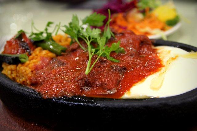 Iskender Kebap mit Bulgur, Tomatensoße und Joghurt.